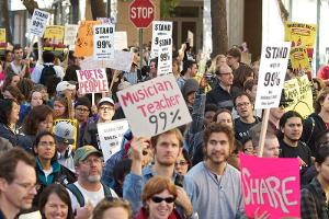 "Protesters in Oakland hold placards with the ""we are the 99%"" theme"