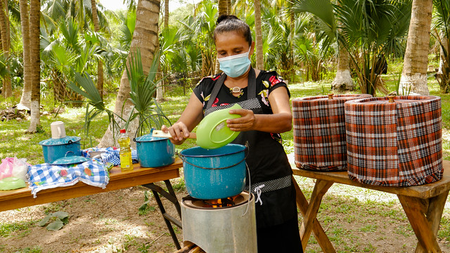 María del Carmen Rodríguez cooks rice on a rocket stove using a few twigs from a tree species that emits less CO2 than mangroves, whose sustainability is also preserved thanks to the use of the tree. Many families in the community of El Salamar have benefited from this energy-efficient technology, as well as other initiatives promoted along the Pacific coast in southern El Salvador. CREDIT: Edgardo Ayala /IPS