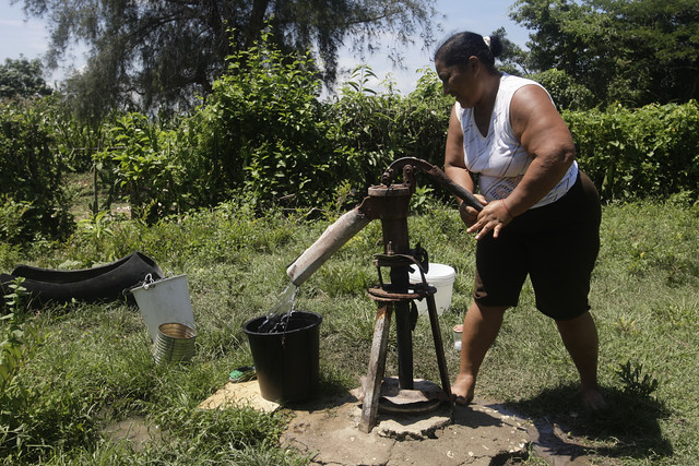 A woman operates a hand pump to draw water for household chores in the Martha Abreu Basic Production Unit community in the central province of Cienfuegos. Projected increased dry periods in Cuba, due to the climate crisis, calls for stimulating initiatives for greater harvesting of rainfall, as well as encouraging the saving and reuse of water. CREDIT: Jorge Luis Baños/IPS