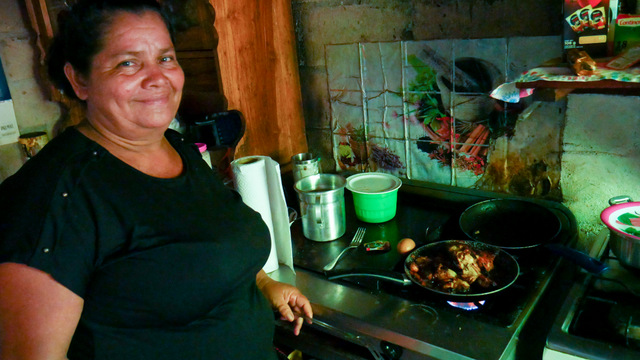 """María Ángela (""""Angelita"""") Cortés, 52, prepares a dish in her mini-restaurant on the beach of Punta Remedios, in the hamlet of Los Cóbanos on El Salvador's Pacific coast. She takes advantage of the return of tourists to boost her business in an area with few job opportunities besides fishing, which is increasingly scarce due to the damage suffered by the local coral reef. CREDIT: Edgardo Ayala/IPS"""