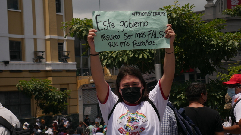 """Holding a sign reading """"This government turned out to be more fake than my eyelashes,"""" a young trans woman participates in the march called by social organisations on Sept. 15 to protest against President Nayib Bukele and his style of government that, since June 2019, has been dismantling democratic institutions in this Central American nation. CREDIT: Edgardo Ayala/IPS"""